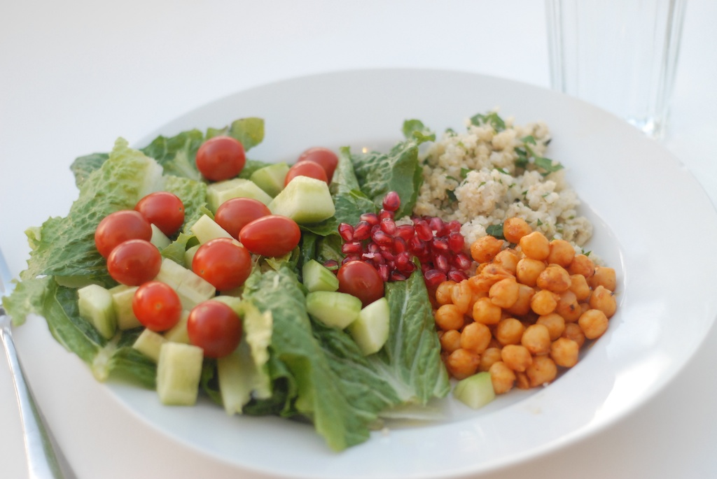Middle Eastern plate with chickpeas, quinoa tabbouleh, tomato and cucumber salad