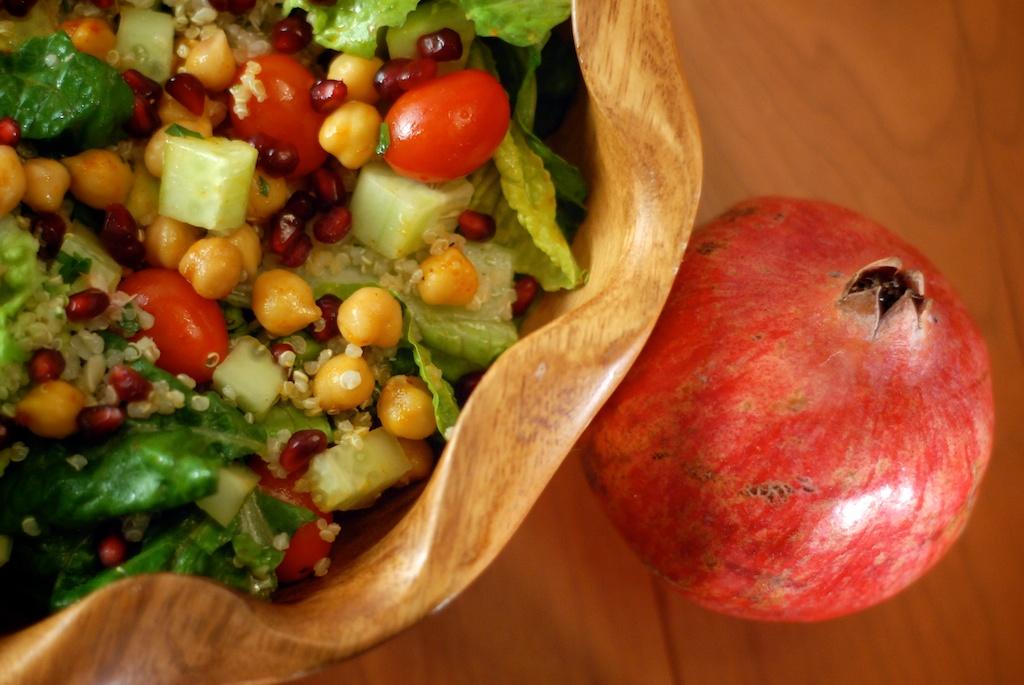 Winter dinner salad with romaine, chickpeas, cucumber, tomato, quinoa tabbouleh, pomegranate