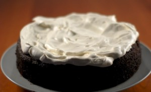 chocolate porter cake with whipped cream topping on a dinner plate