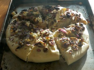 Greek lagana with olives and rosemary shown on a baking pan