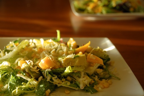 mango avocado and corn salad with grated cheese and creamy ginger dressing
