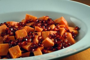 papaya and pomegranate salad in a white serving dish