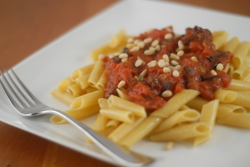 pasta puttanesca with pine nut garnish