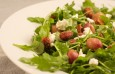 Fresh green arugula salad with mild goat cheese, candied hazelnuts, and roasted grapes